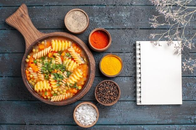 ダークデスクのスープ色のイタリアンパスタ料理にさまざまな調味料を加えたスパイラルイタリアンパスタからのトップビューのおいしいパスタスープ