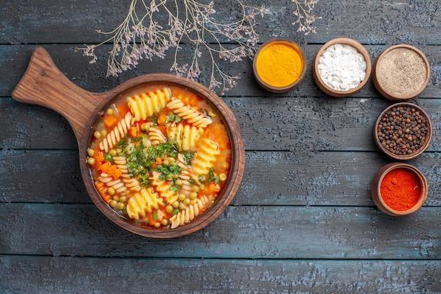 ダークデスクのスープ色のイタリアンパスタ料理にさまざまな調味料を加えたスパイラルイタリアンパスタのトップビューおいしいパスタスープ