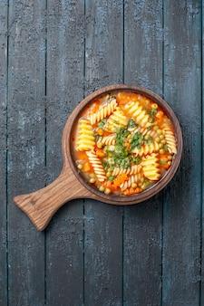 Vista dall'alto gustosa zuppa di pasta da pasta italiana a spirale con verdure su piatto da cucina blu scuro da tavolo zuppa italiana di pasta colorata