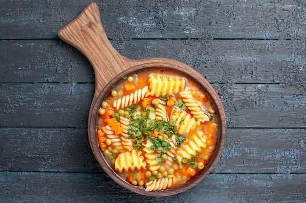 Vista dall'alto gustosa zuppa di pasta da pasta italiana a spirale con verdure su piatto da cucina blu scuro da tavolo zuppa italiana di pasta colorata Foto Gratuite