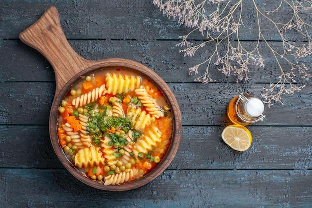 Vista dall'alto gustosa zuppa di pasta da pasta italiana a spirale con verdure sul piatto di cucina di pasta italiana color zuppa di scrivania blu scuro