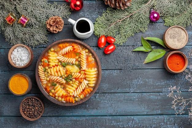 Vista dall'alto gustosa zuppa di pasta da pasta italiana a spirale con condimenti su un piatto di pasta colorata da tavolo rustico blu scuro