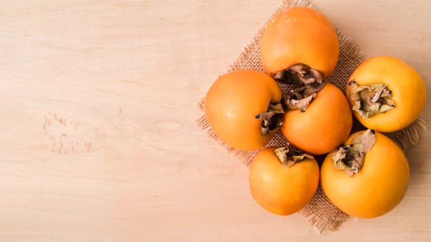 Top view tasty persimmons with copy space