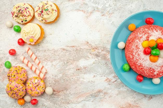 밝은 흰색 표면에 쿠키가 있는 맛있는 분홍색 케이크 레인보우 캔디 디저트 컬러 케이크