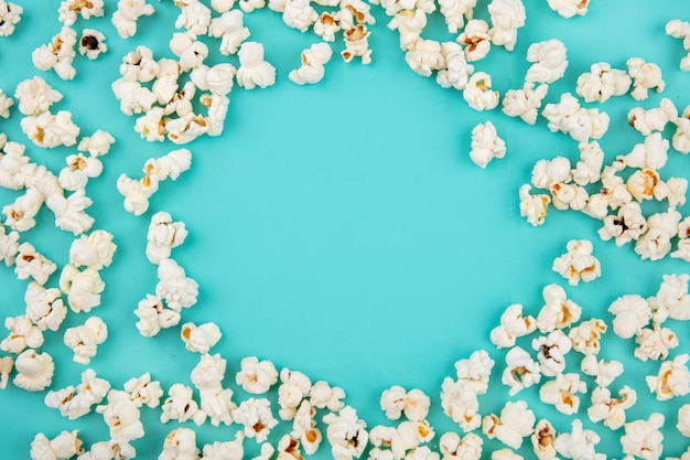 Top view of tasty popcorn isolated on blue surface