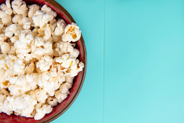 Top view of tasty popcorn on a wooden bowl on blue surface