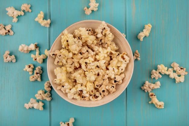 Vista dall'alto di gustosi popcorn su una ciotola su un tavolo di legno blu