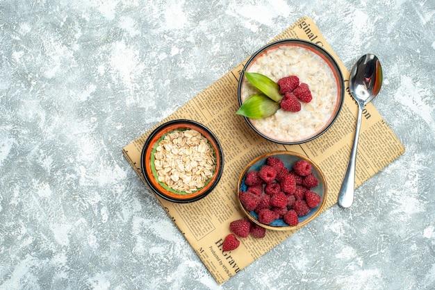 Top view of tasty porridge with raspberries on light surface