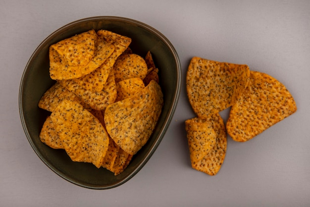 Top view of tasty potato chips on a bowl with chips isolated