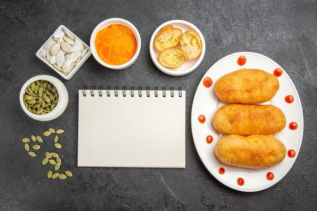 Vista dall'alto gustose focacce di patate con purea di zucca e i suoi semi su sfondo grigio scuro torta di torta di patate fritte olio di farina