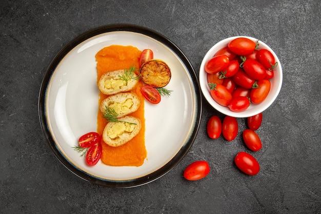 灰色の背景にカボチャとフレッシュトマトを添えたトップビューのおいしいポテトパイオーブン焼き色皿ディナースライス
