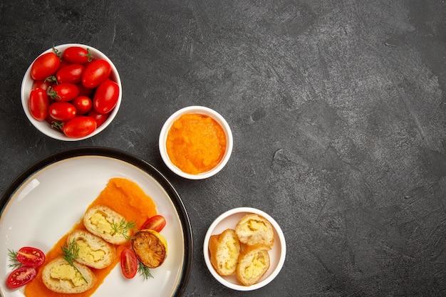 灰色の机の上のカボチャとフレッシュトマトのトップビューおいしいポテトパイディナーオーブン焼き色皿スライス