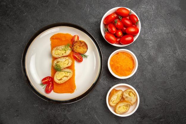 灰色の机のオーブンでカボチャとフレッシュトマトを添えたトップビューのおいしいポテトパイ焼き色皿ディナースライス