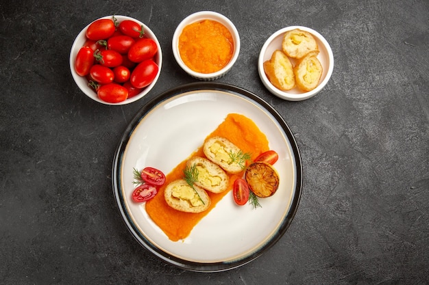 灰色の背景にカボチャとフレッシュトマトのトップビューおいしいポテトパイディナーオーブン焼き色皿スライス