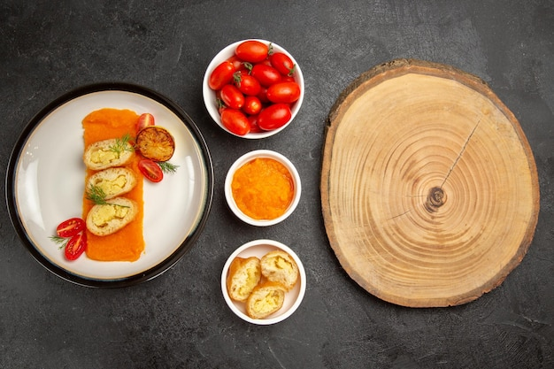 Top view tasty potato pies with pumpkin and fresh tomatoes on a grey background dinner oven bake color dish slice