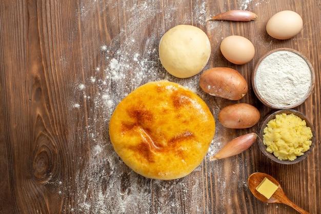Вид сверху вкусный тыквенный пирог с мукой и яйцами на коричневом деревянном столе, пирог, горячий пирог, печь