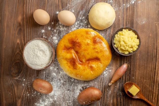 茶色の木製の机の上の小麦粉とおいしいパンプキンパイの上面図パイケーキホットケーキ焼きオーブン
