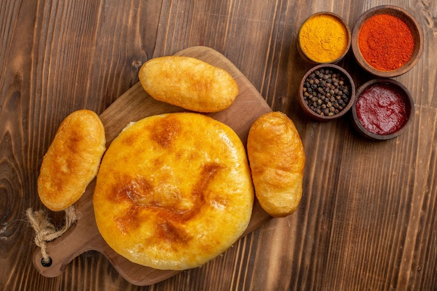 茶色の木製の机の上のジャガイモのホットケーキとおいしいパンプキンパイの上面図パイケーキホットケーキ焼きオーブン
