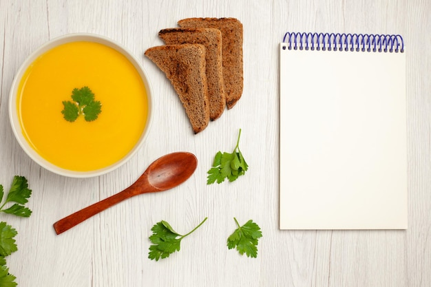 Top view of tasty pumpkin soup cream textured with dark bread loafs on light white