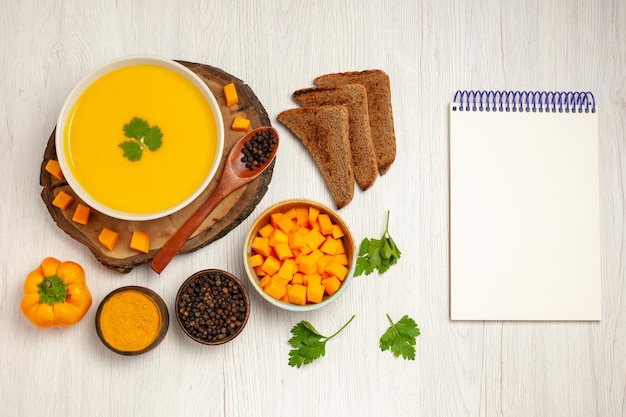 Top view of tasty pumpkin soup cream textured with dark bread loafs on white floor vegetable soup dish meal sauce