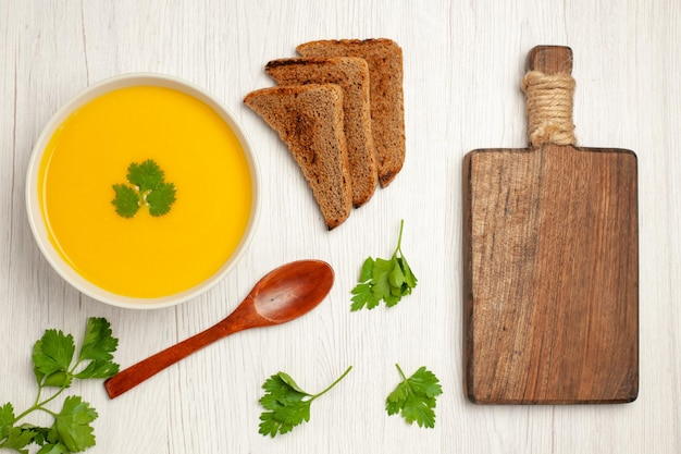 Top view of tasty pumpkin soup cream textured with dark bread loafs on white