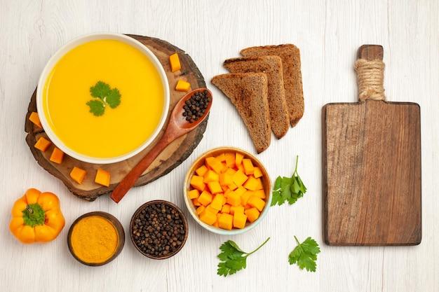 Vista dall'alto di una gustosa zuppa di zucca con pagnotte di pane scuro e condimenti su bianco