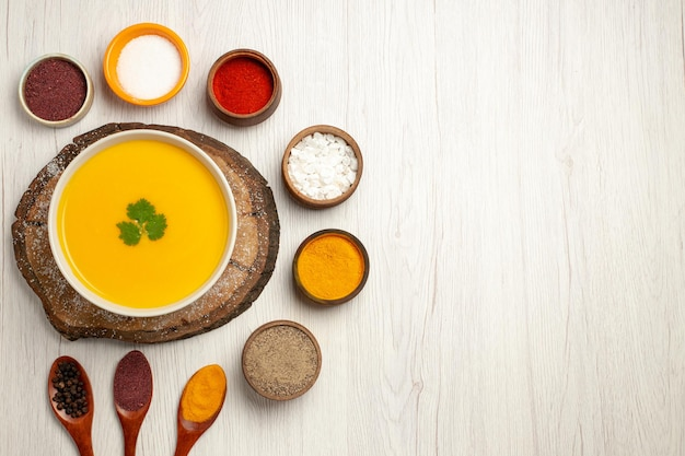 Top view of tasty pumpkin soup with different seasonings on white