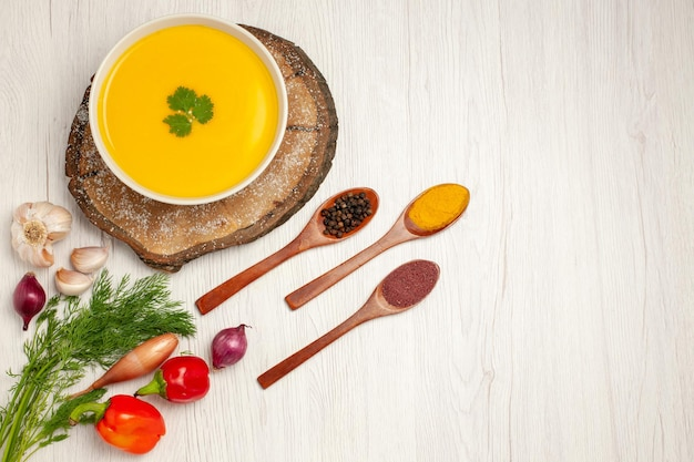 Top view of tasty pumpkin soup with greens on white