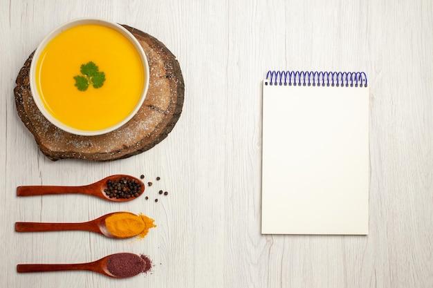 Vista dall'alto di una gustosa zuppa di zucca con pepe su bianco