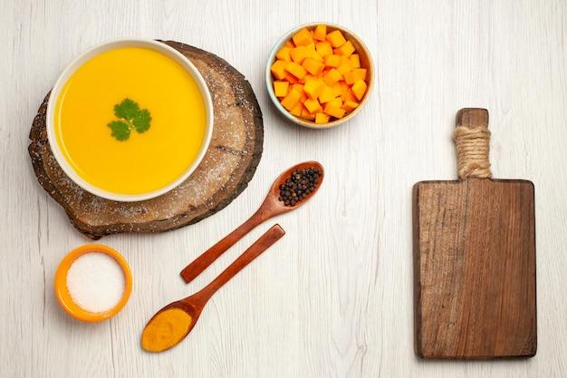 Vista dall'alto di una gustosa zuppa di zucca con condimenti su bianco