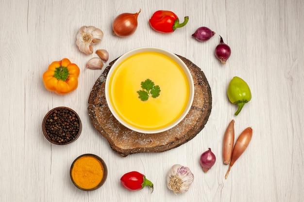 Vista dall'alto di una gustosa zuppa di zucca con verdure su bianco