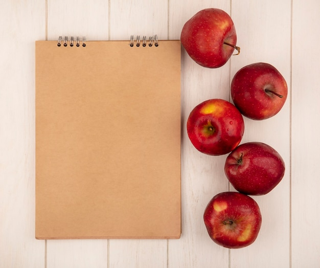 Top view of tasty red apples isolated on a white wooden surface with copy space