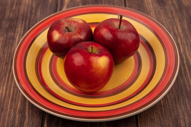 Vista dall'alto di gustose mele rosse su un piatto su una superficie di legno
