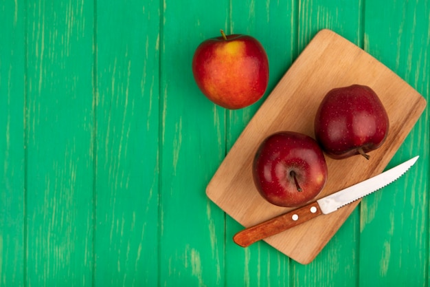 Vista dall'alto di gustose mele rosse su una tavola da cucina in legno con coltello su una superficie di legno verde con spazio di copia