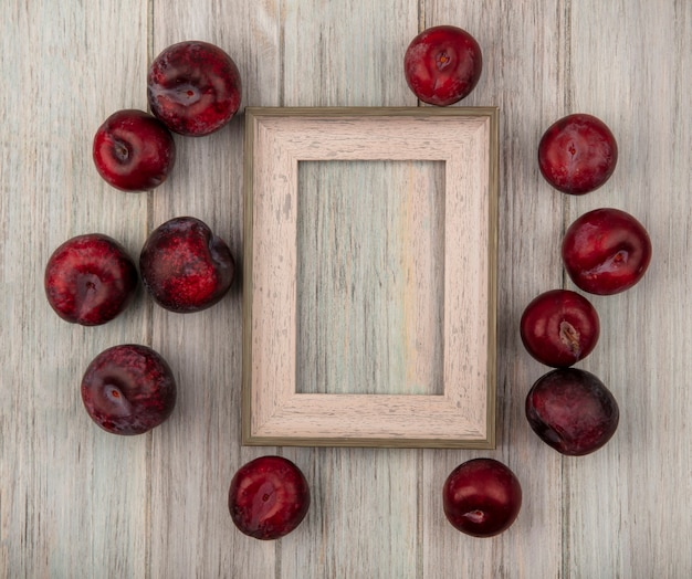 Top view of tasty ripe pluots isolated on a grey wooden surface with copy space