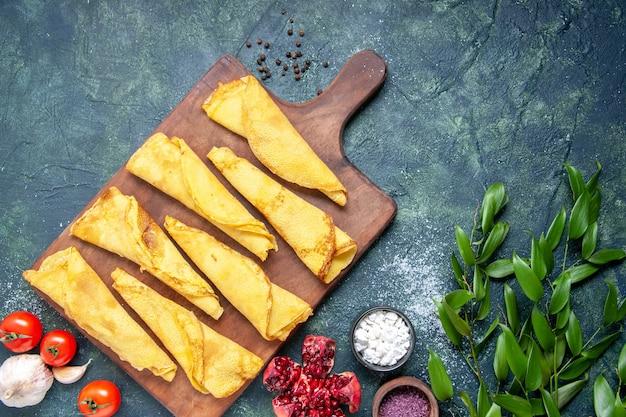 Vista dall'alto gustose frittelle arrotolate su sfondo scuro colore pasto torta di carne pasticceria hotcake pasta torta dolce