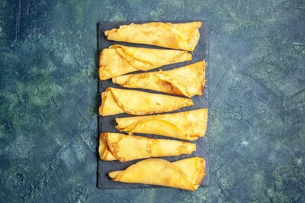 Вид сверху вкусные блинчики, выложенные на темном фоне цветная еда пирог мясо выпечка тесто торт сладкий хоткейк