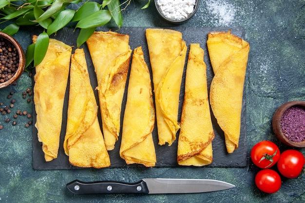 Vista dall'alto gustose frittelle arrotolate foderate con pomodori sullo sfondo scuro torta di farina di colore pasta di carne torta di pasticceria dolce torta calda