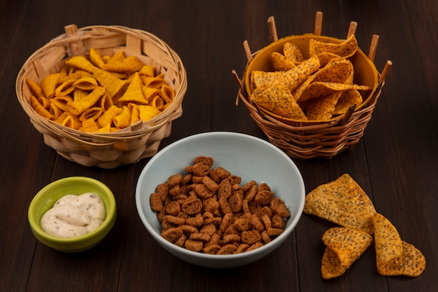 Top view of tasty rye rusks on a bowl with spicy chips on a bucket with sauce on a bowl on a wooden table