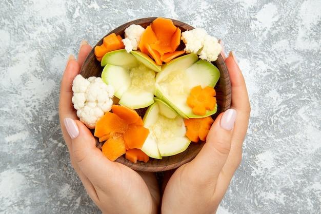 Vista dall'alto gustosa insalata all'interno della piastra su sfondo bianco pasto salute insalata di verdure