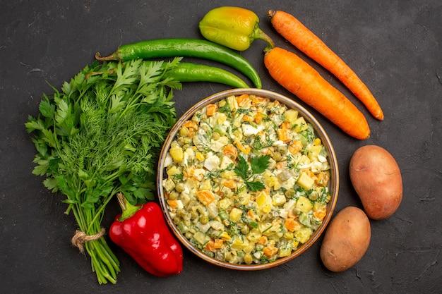 Вид сверху вкусный салат с зеленью и свежими овощами на темном фоне