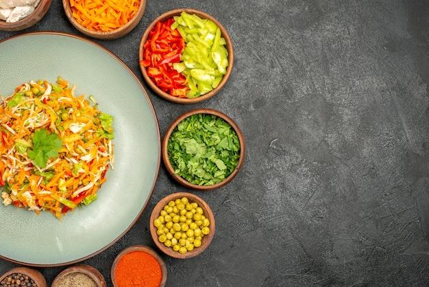 Вид сверху вкусный салат с ингредиентами на темно-серой диетической диете