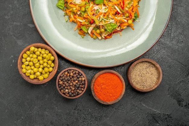 Top view tasty salad with seasonings on the grey salad food health diet