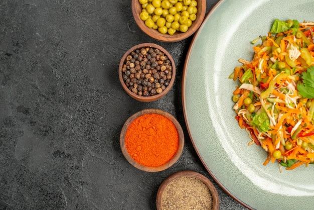 Вид сверху вкусный салат с приправами на сером здоровом салате