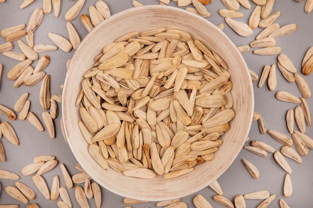 Vista dall'alto di semi di girasole bianchi gustosi e salati su una ciotola con semi di girasole isolati