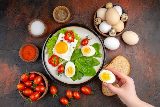 暗いテーブルの上に調理された卵とトマトの上面図おいしいサンドイッチ