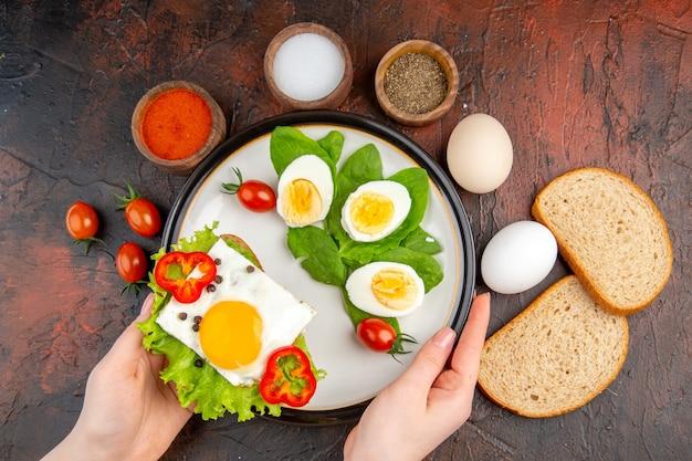 暗いテーブルの上に卵の調味料とトマトのトップビューおいしいサンドイッチ