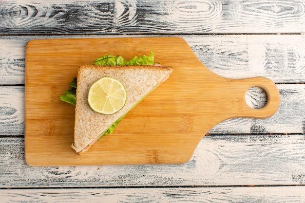 Vista dall'alto di un gustoso panino con insalata verde prosciutto e pomodori