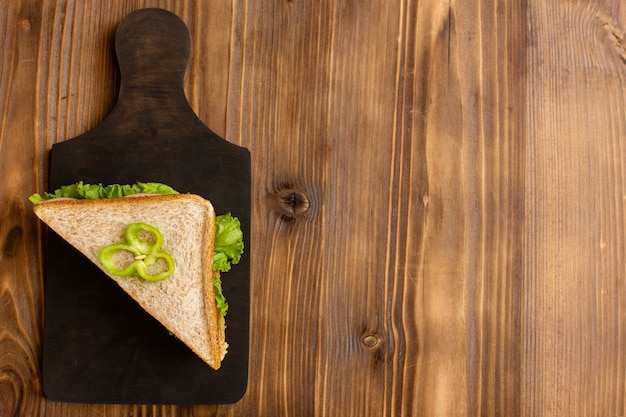 Top view of tasty sandwich with green salad tomatoes on the brown wooden surface