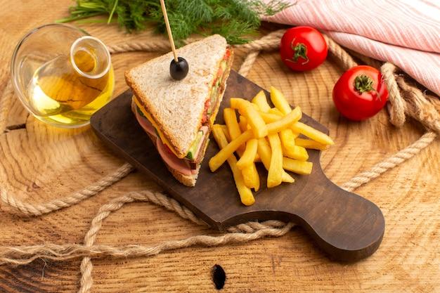 Вид сверху вкусный бутерброд с оливками, ветчиной, помидорами, овощами вместе с картофелем фри, веревками, маслом, красными помидорами на деревянном фоне, сэндвич, еда, закуска, завтрак